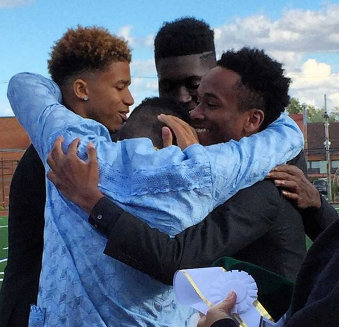 The Elmont Memorial High School 2015 Homecoming Court embraces Joseph Olawoye (blue shirt) after he is declared the 2015 Homecoming King. (Photo by Heather Doyle for Newsday, Oct. 17, 2015)